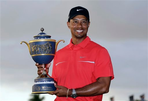 Tiger Woods holds the Gene Sarazen Cup for winning the Cadillac Championship golf tournament on Sunday, March 10, 2013, in Doral, Fla.