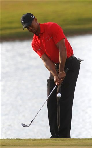 Tiger Woods hits from the rough on the 18th holde during the third round of the Cadillac Championship golf tournament Sunday, March 10, 2013, in Doral, Fla.