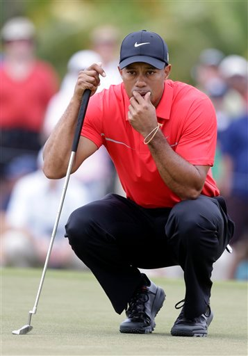 Tiger Woods looks back to catch a ball after his caddie cleaned it on the eighth green during the final round of the Cadillac Championship golf tournament on Sunday, March 10, 2013, in Doral, Fla.