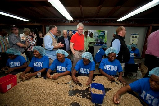 Former U.S. President and UN special envoy to Haiti, Bill Clinton watches workers sort coffee beans during a visit to the coffee production and export company Rebo S.A. in Port-au-Prince, Haiti. Monday March. 11, 2013.