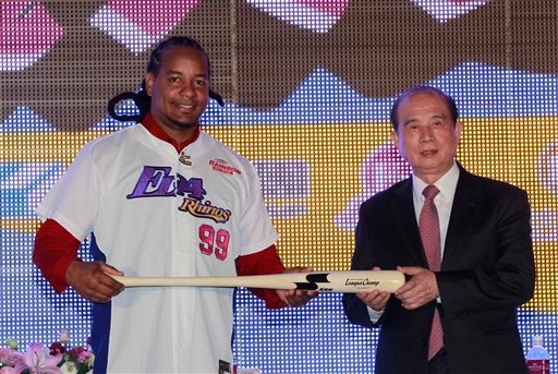 ? Former MLB star Manny Ramirez, left, and head of E-United Group Lin Yi-shou pose for media holding an honorary baseball bat after signing a short-term contract to play on the EDA Rhinos in Taiwan's professional baseball league in Kaohsiung, Taiwan.