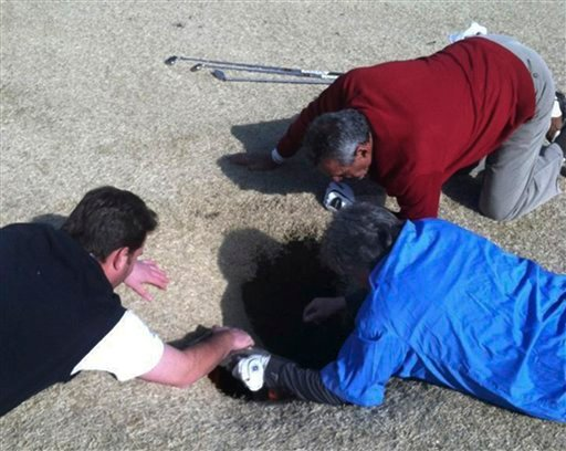 In this cell phone image taken March 8, 2013 and provided by golfmanna.com, Hank Martinez, top, Ed Magaletta, right, and Russ Nobbe, look into an 18-foot-deep and 10-foot- wide sinkhole that golfer Mark Minhal fell into.