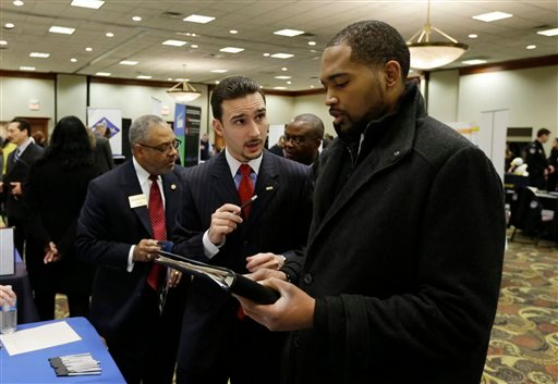 In this Feb. 28, 2013 photo Robin Basil, left, of the Garland-Hill insurance agency talks with college student Markell Easter at the JobFairGiant.com employment fair in Dearborn, Mich. (AP)