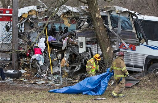 ? Rescue personnel remove a tarp after a tour bus crash on the Pennsylvania Turnpike on Saturday, March 16, 2013 near Carlisle, Pa.
