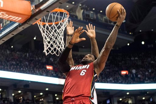 ? Miami Heat's LeBron James scores on Toronto Raptors' Amir Johnson during first half NBA basketball action in Toronto on Sunday, March 17, 2013. (AP Photo/THE CANADIAN PRESS,Chris Young)