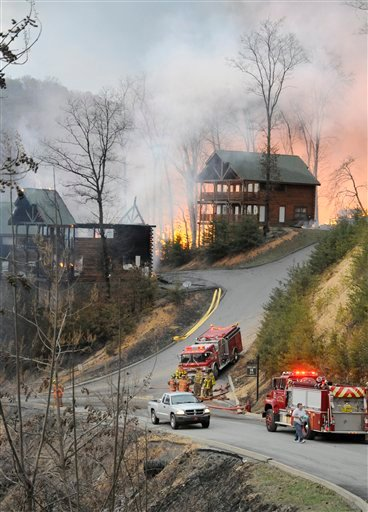 ? Firefighters set a boundary as cabins burn on Black Bear Cub Way in Sevier County, Tenn Sunday March 17, 2013.