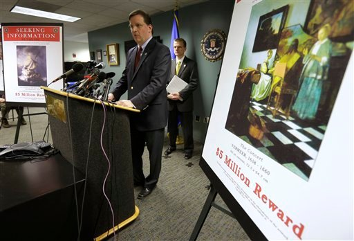 ? Anthony Amore, chief of security at the Gardner Museum, center, stands next to a poster that shows an image of a Vermeer painting and lists a reward, right, while facing reporters during a news conference at FBI headquarters in Boston, Monday, March 18.