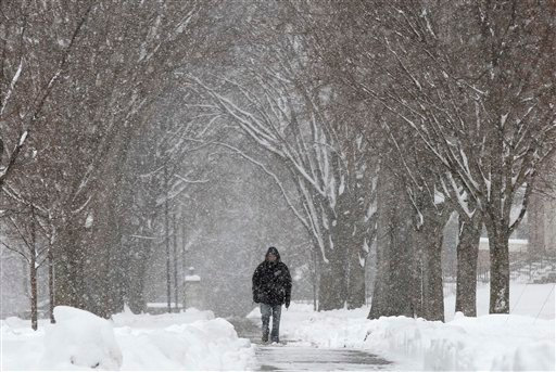 A pedestrian walks through the campus of Phillips Academy during a winter storm in Andover, Mass. Tuesday, March 19, 2013. (AP)