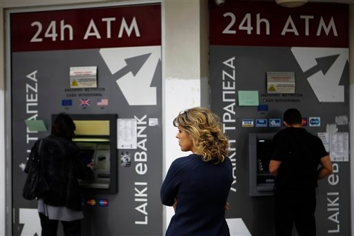  A woman waits as two people use the ATM machines in central capital Nicosia, Cyprus, Friday, March 22, 2013.
