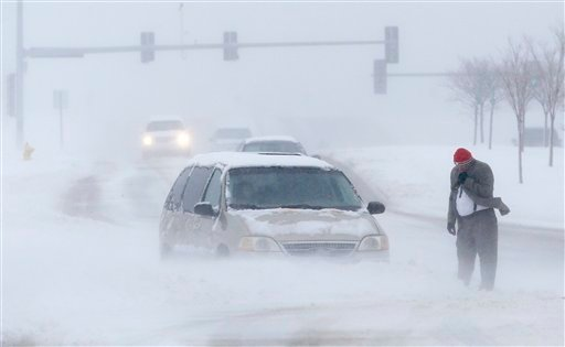 © A man waits for help after becoming stuck in snow along West 6th Street in Lawrence, Kan., Sunday, March 24, 2013. Few signs of spring are being found in parts of the Midwest as a snowstorm brings heavy snow and high winds. (AP Photo/Orlin Wagner)