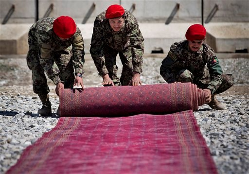 Afghan National Army soldiers roll up the red carpet after the hand over ceremony of the Parwan Detention Facility from U.S. military control to Afghan authorities in Bagram, outside Kabul, Afghanistan, Monday, March 25, 2013.