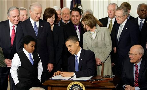 FILE - In this March 23, 2010 file photo, Marcelas Owens of Seattle, left, Rep. John Dingell, D-Mich., right, and others, look on as President Barack Obama signs the health care bill in the East Room of the White House in Washington. (AP)