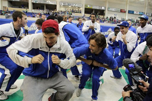 In this photo taken, Monday, March 25, 2013, Florida Gulf Coast Filip Cvjeticanin, center, flanked by Chase Fieler, left, and Christophe Varidel, do the Eagle dance during a pep rally for the men's basketball team at Alico Arena in Fort Myers, Fla. (AP)