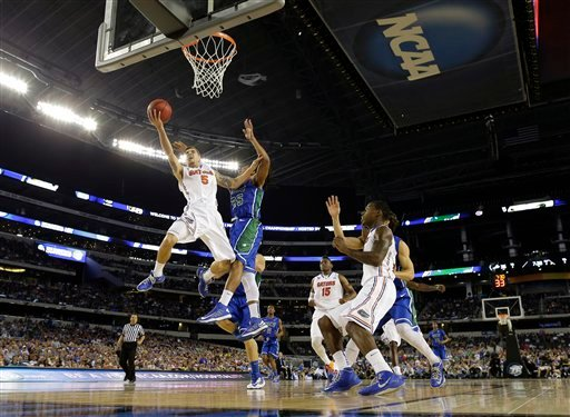 Florida's Scottie Wilbekin (5) shoots as Florida Gulf Coast's Sherwood Brown (25) defends during the second half of a regional semifinal game in the NCAA college basketball tournament, Saturday, March 30, 2013, in Arlington, Texas.