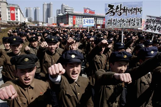 University students punch the air as they march through Kim Il Sung Square in downtown Pyongyang, North Korea, Friday, March 29, 2013.