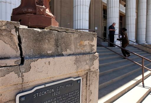 In this June 26, 2012 file photo, a light standard rests at the dilapidated entrance to city hall in Stockton, Calif.