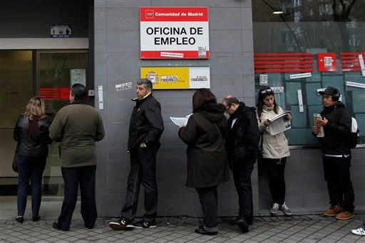 People wait outside an unemployment office in Madrid, Spain, Tuesday, April 2, 2013.