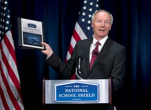 National School Shield Task Force Director, former Arkansas Rep. Asa Hutchinson, holds a copy of group's study during a news conference at National Press Club in Washington, Tuesday, April 2, 2013. (AP)