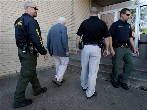 Kaufman county law enforcement officials escort an employee inside the county courthouse Monday, April 1, 2013, in Kaufman, Texas. (AP)