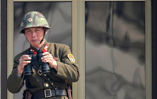 A North Korean soldier watches the South Korean side at the border village of Panmunjom in the demilitarized zone (DMZ) in South Korea Thursday, April 4, 2013. (AP Photo/Yonhap, Lee Jong-hoon)
