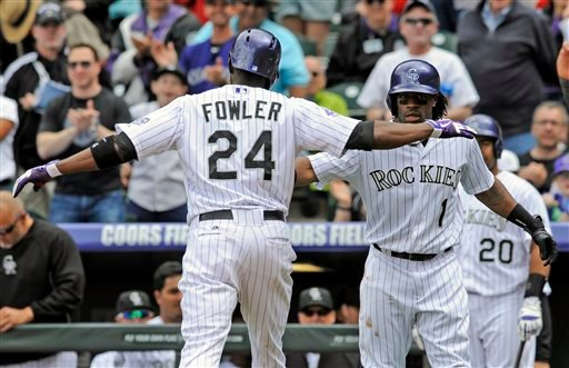 Colorado Rockies' Dexter Fowler (24) celebrates a two-run home run off San Diego Padres starting pitcher Edinson Volquez with teammate Eric Young Jr. (1) during the first inning of a baseball game on Sunday, April 7, 2013, in Denver.