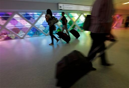 In this Thursday, Sept. 27, 2012 photo, passengers travel through an airport in Miami.