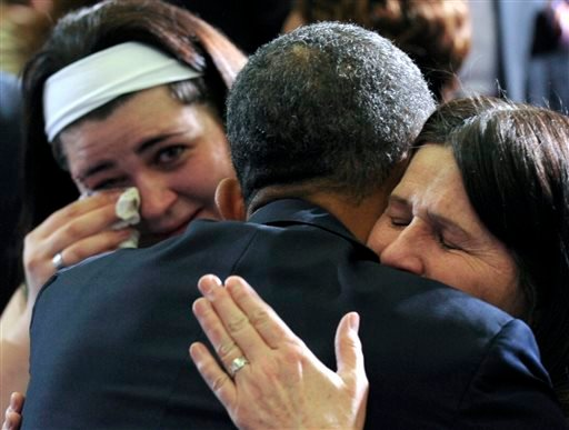 President Barack Obama hugs Newtown, Conn., family members after speaking at the University of Hartford in Hartford, Conn., Monday, April 8, 2013.