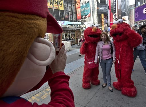 A Super Mario character, left, uses a woman's mobile phone camera to photographer her with a pair of Elmo characters in New York's Times Square, Tuesday, April 9, 2013. (AP)