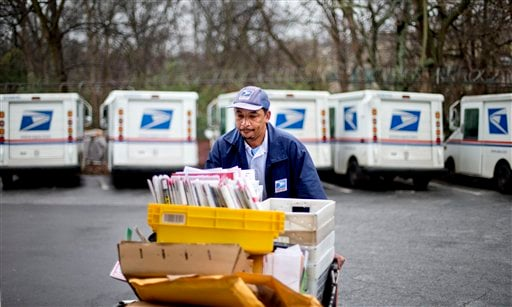 Feb. 7, 2013 file photo: U.S. Postal Service letter carrier Michael McDonald gathers mail to load into his truck before making his delivery run in the East Atlanta neighborhood, in Atlanta. (AP Photo/David Goldman)
