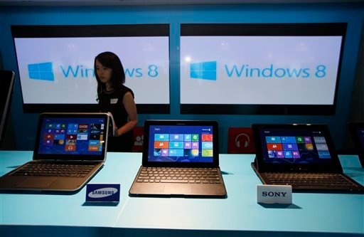 FILE - In this Friday, Oct. 26, 2012, file photo, a woman walks past laptop computers running Microsoft Windows 8 operating system during its launching ceremony in Hong Kong. (AP)