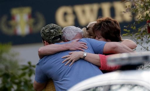 A group of people huddle together after an explosion and gunshots were heard near the scene where a man was holding four firefighters hostage Wednesday, April 10, 2013 in Suwanee, Ga.