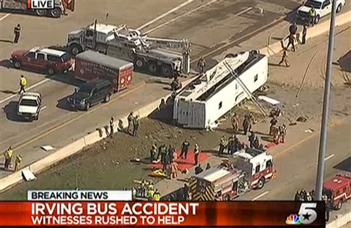 This frame grab provided by KXAS-TV shows emergency personnel at the scene where a chartered bus overturned on a highway near Dallas-Fort Worth International Airport in Irving, Texas. (AP Photo/Courtesy KXAS-TV)