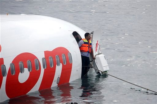 In this photo released by Indonesian Police, the wreckage of a crashed Lion Air plane sits on the water near the airport in Bali, Indonesia on Saturday, April 13, 2013.