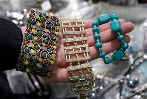 In this Dec. 13, 2011, file photo, a California Department of Justice employee holds up counterfeit jewelry that was confiscated during an investigation before it was sold on eBay during a news conference in San Jose, Calif.