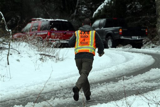 A man with King County Search and Rescue runs toward scene of avalanche at exit 47 along I-90 near Snoqualmie Pass, Sat. April 13, 2013.
