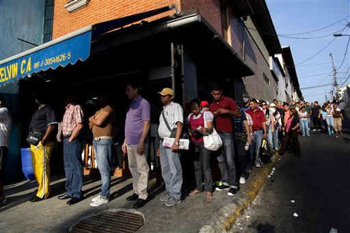 Residents wait in line to enter a polling station to vote in the presidential election in Caracas, Venezuela, early Sunday, April 14, 2013.