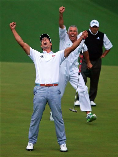 Adam Scott and his caddie Steve Williams reacts to his putt dropping on the second hole of a playoff to win the Masters golf tournament, Sunday, April 14, 2013, in Augusta.