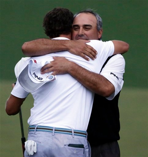 Angel Cabrera, right, of Argentina, hugs Adam Scott, of Australia, after Scott made a birdie putt on the second playoff hole to win the Masters golf tournament Sunday, April 14, 2013, in Augusta, Ga.