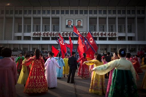 A man, center, supervises a dancing group during a mass folk dance in front of the Pyongyang Indoor Stadium in Pyongyang, North Korea, Monday, April 15, 2013. (AP Photo/Alexander F. Yuan)
