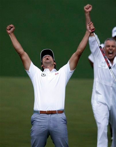 Adam Scott, of Australia, celebrates with caddie Steve Williams after making a birdie putt on the second playoff hole to win the Masters golf tournament Sunday, April 14, 2013, in Augusta, Ga. (AP Photo/David Goldman)