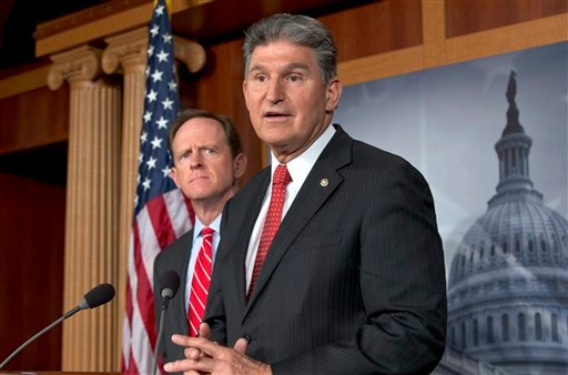 In this April 10, 2013 file photo, Sen. Joe Manchin, D-W.Va., right, accompanied by Sen. Patrick Toomey, R-Pa., announce that they have reached a bipartisan deal on expanding background checks to more gun buyers,, on Capitol Hill in Washington.