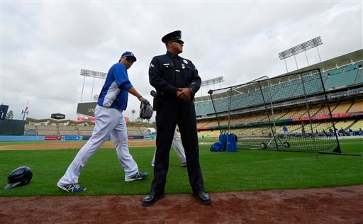 Los Angeles Dodgers starting pitcher Hyun-Jin Ryu, left, of South Korea, walks by a police officer during batting practice before their baseball game against the San Diego Padres, Monday, April 15, 2013, in Los Angeles. (AP Photo/Mark J. Terrill)