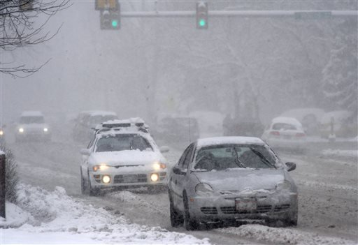 Motorist travel on West Mulberry Road at Shields Road in Fort Collins as snow falls in Fort Collins, Colo., Monday April 15, 2013. (AP Photo/The Coloradoan, V. Richard Haro)