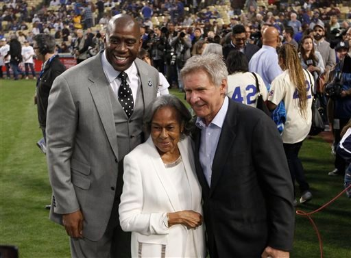 Los Angeles Dodgers owner Magic Johnson, left, Rachel Robinson, widow of baseball player Jackie Robinson, center, and actor Harrison Ford pose for photos during a Jackie Robinson Day ceremony before a baseball game against the San Diego Padres in L.A.
