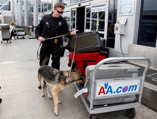 Security checks passengers bags at the American airlines terminal at Los Angeles International Airport on Tuesday, April 16, 2013. (AP Photo/Nick Ut)