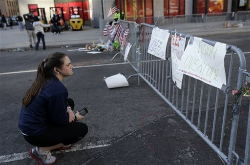 Cailly Carroll reads signs posted on a barricade, Wednesday, April 17, 2013, in Boston. The city continues to cope following Monday's explosions near the finish line of the Boston Marathon. (AP Photo/Julio Cortez)