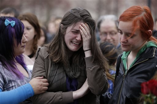 Emma MacDonald, 21, center, cries during a vigil for the victims of the Boston Marathon explosions at Boston Common, Tuesday, April 16, 2013. (AP Photo/Julio Cortez)