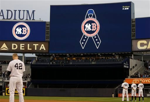 New York Yankees players observe a moment of silence in memory of the victims of the Boston Marathon explosions before a baseball game against the Arizona Diamondbacks at Yankee Stadium April 16, 2013. (AP Photo/Kathy Willens)
