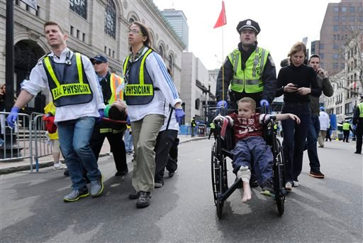 A Boston police officer wheels in injured boy down Boylston Street as medical workers carry an injured runner following an explosion during the 2013 Boston Marathon in Boston, Monday, April 15, 2013. (AP Photo/Charles Krupa)