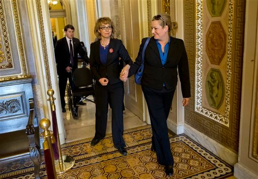 Former Arizona Rep. Gabrielle Giffords, center, is escorted in the hallway outside the Senate Chamber on Capitol Hill in Washington, Wednesday, April 17, 2013, before the start of a Senate vote on gun control legislation. (AP)